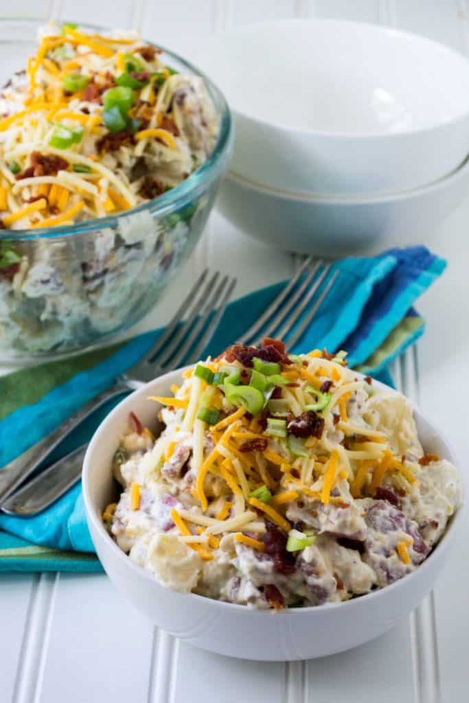 Loaded Potato Salad | Loaded Potato Salad is tender, creamy and fully loaded with tons of cheese, bacon and green onions.. It is the perfect addition to any summertime party. | Pack Momma | https://www.packmomma.com