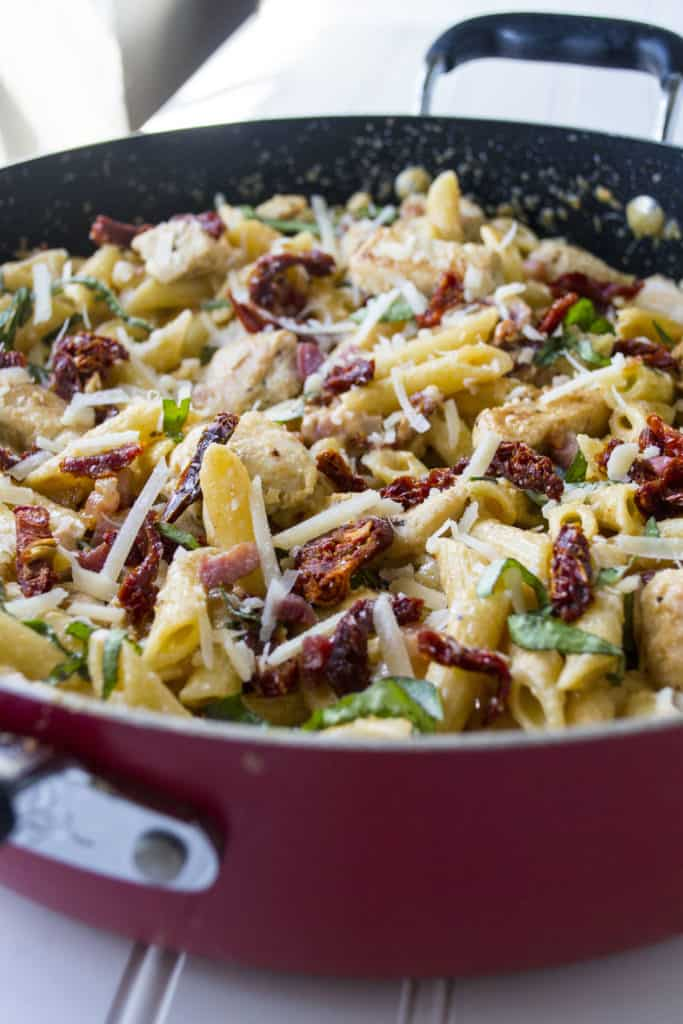 Tuscan Chicken Pasta | Tuscan Chicken Pasta is cheesy, creamy and a little spicy with hearty chicken and pasta mixed with sun dried tomatoes and panchetta. The perfect quick meal | Pack Momma | https://www.packmomma.com